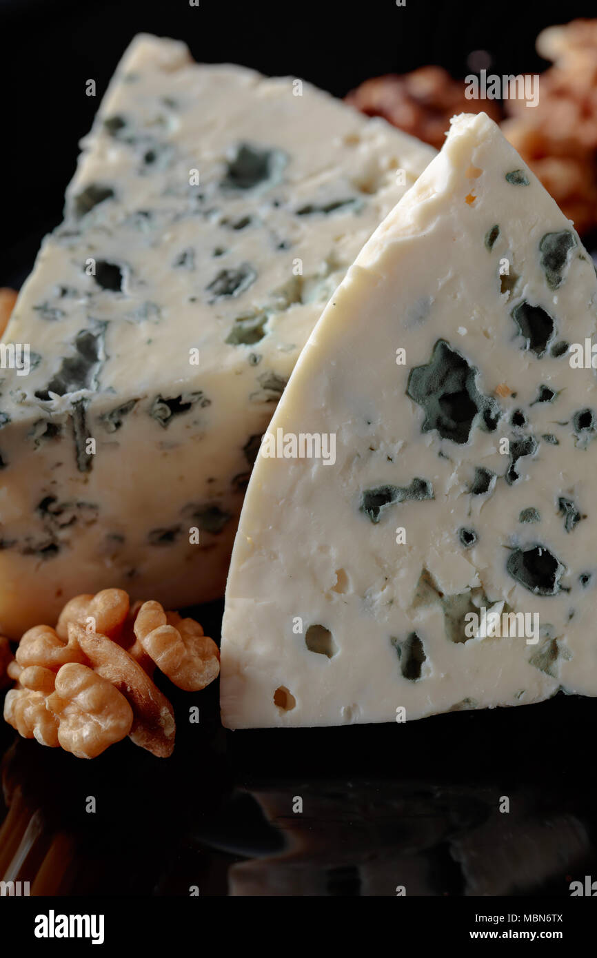 Wedges of soft blue cheese with walnuts on a black plate. - Stock Image