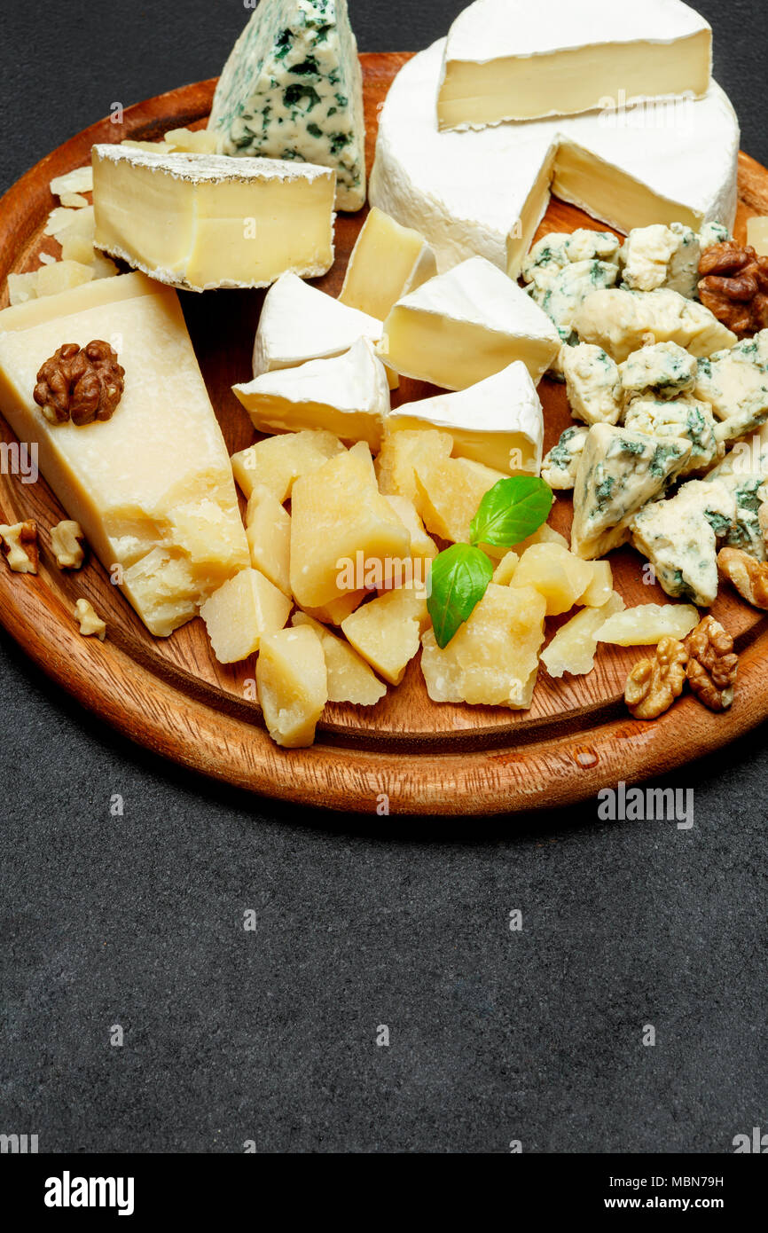 Cheese plate with Assorted cheeses Camembert, Brie, Parmesan blue cheese, goat - Stock Image