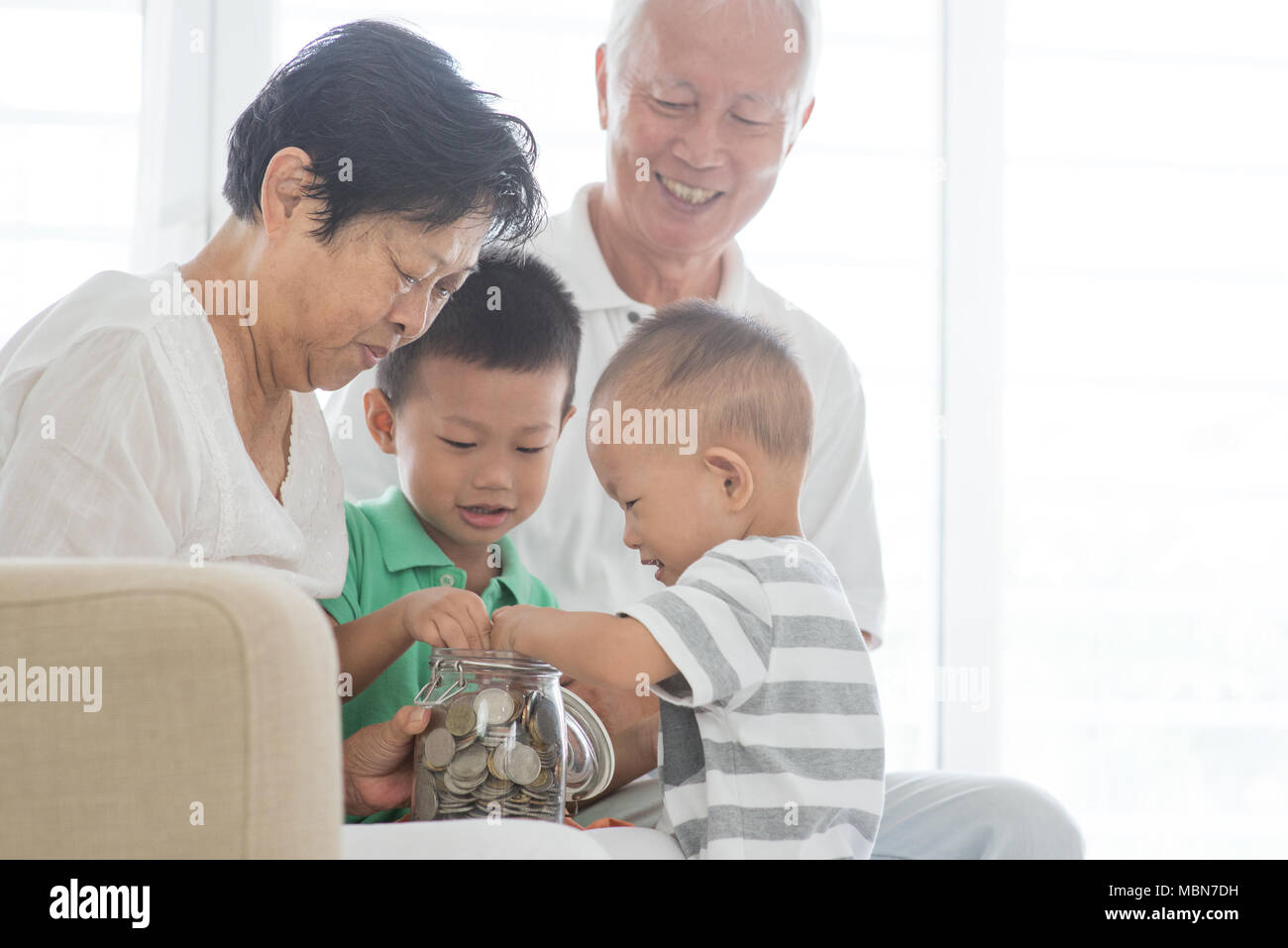 asian elderly and children saving money at home family financial