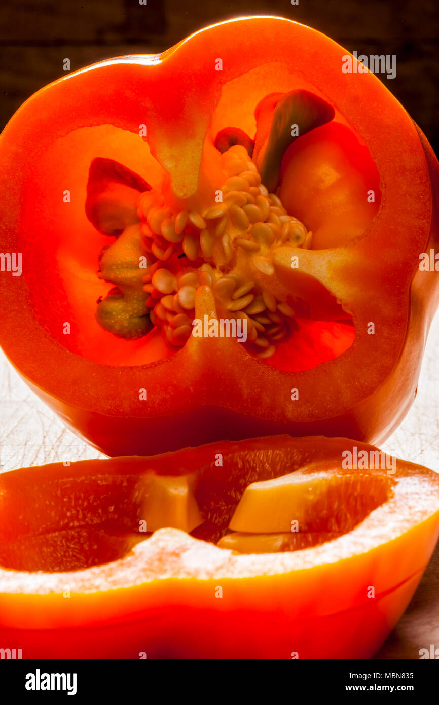 Studio still lifes of an orange bell pepper on a cutting board. - Stock Image