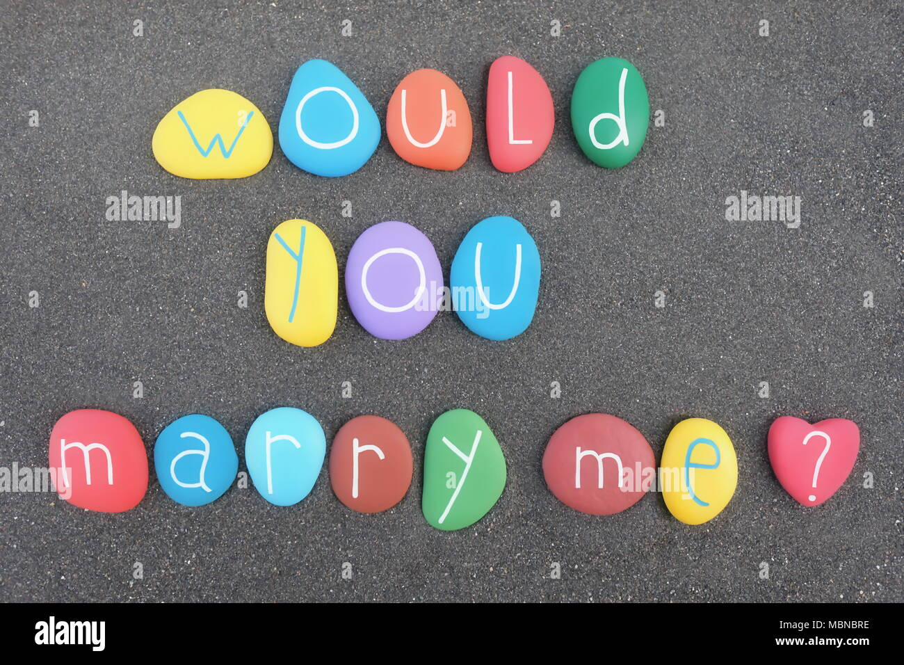 Would you marry me ? Multicolored painted stones phrase over black volcanic sand Stock Photo