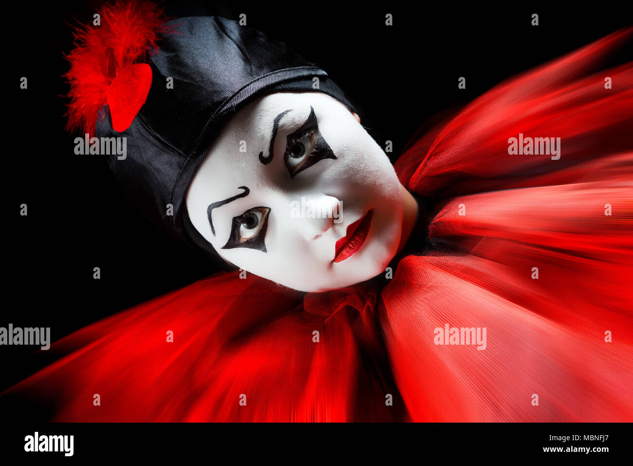 Flashing portrait in red and black of a mime pierrot clown - Stock Image