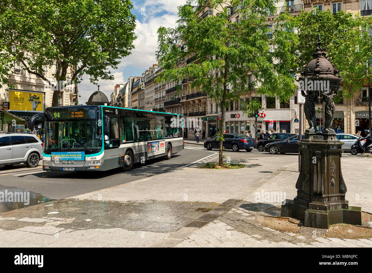 Wallace fountain, public bus and cars on the street of Paris - capital and largest city of France. - Stock Image