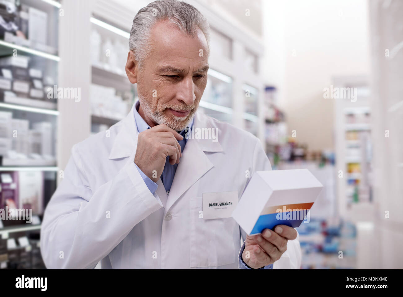 Musing male pharmacist discovering new drug - Stock Image