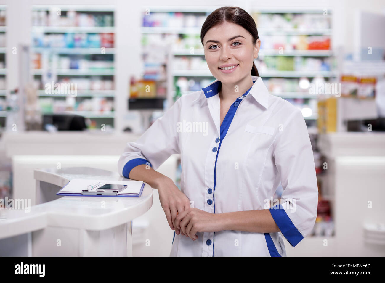Jolly female pharmacist saluting clients - Stock Image