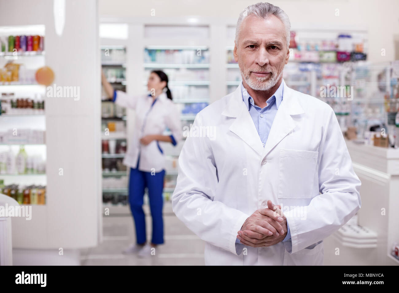 Confident male pharmacist expecting clients - Stock Image