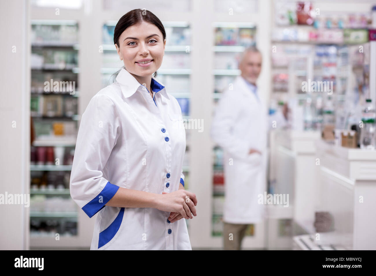 Merry female pharmacist awaiting clients - Stock Image