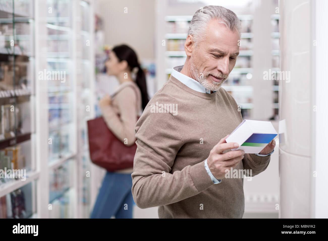 Pleasant senior man selecting medication - Stock Image