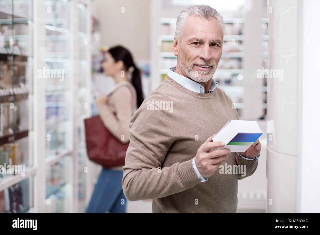 Happy senior man studying drug - Stock Image
