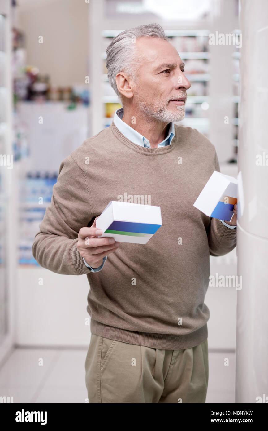 Musing senior man supporting health - Stock Image