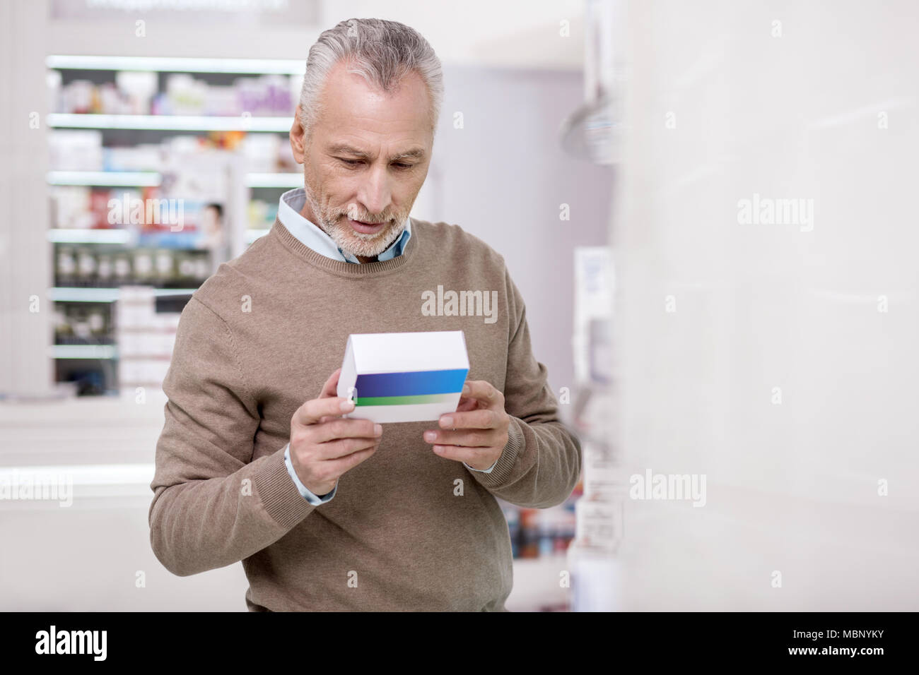 Concentrated senior man examining product - Stock Image