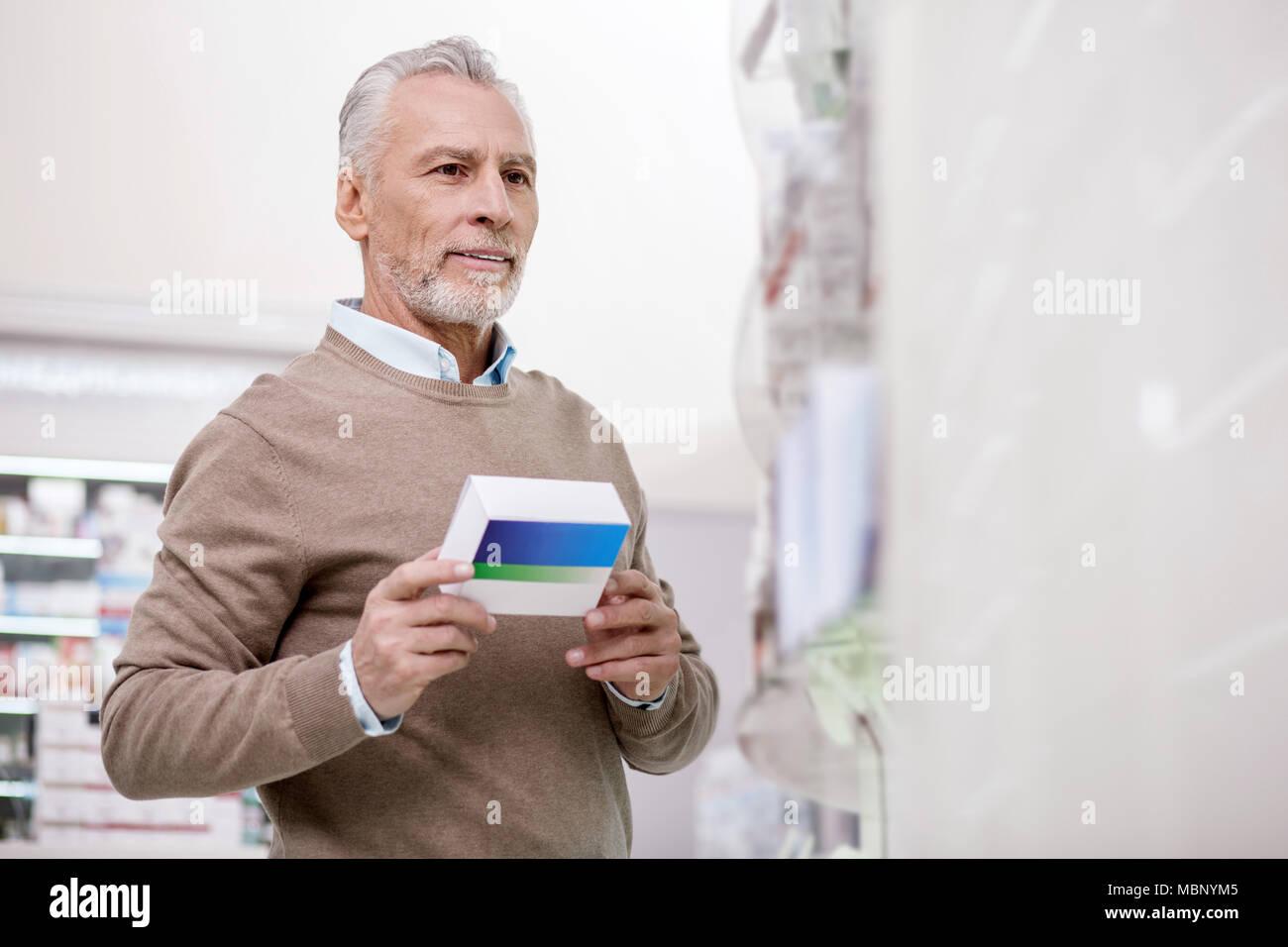 Confident senior man selecting medication - Stock Image