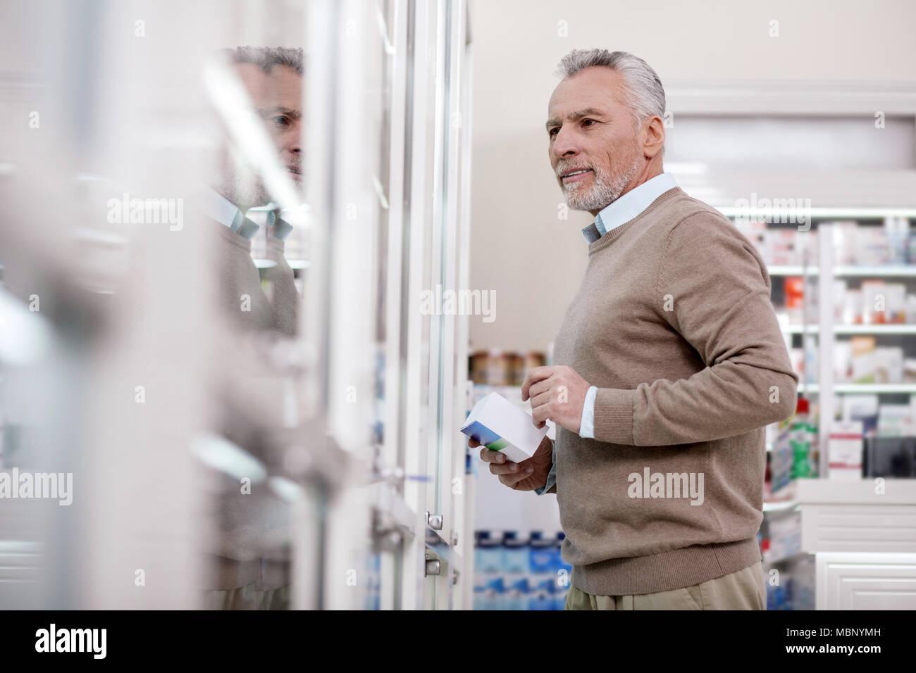 Thoughtful senior man selecting vitamins - Stock Image