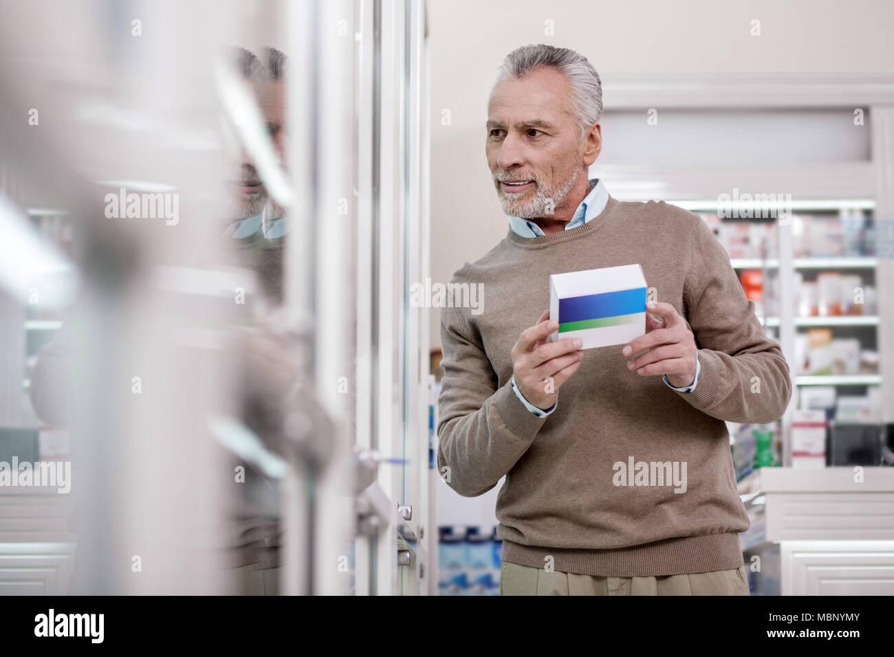 Reflective senior man deciding on vitamins - Stock Image
