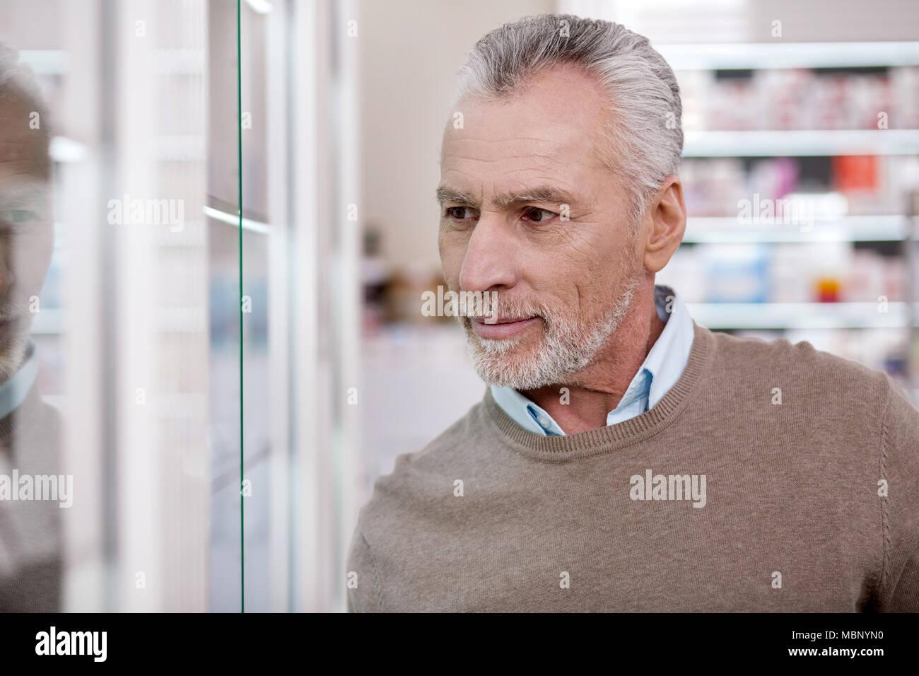 Charming senior man selecting goods - Stock Image
