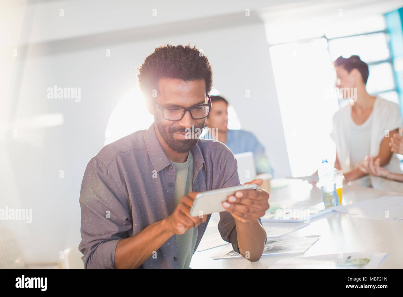 Creative businessman using smart phone in conference room meeting - Stock Image