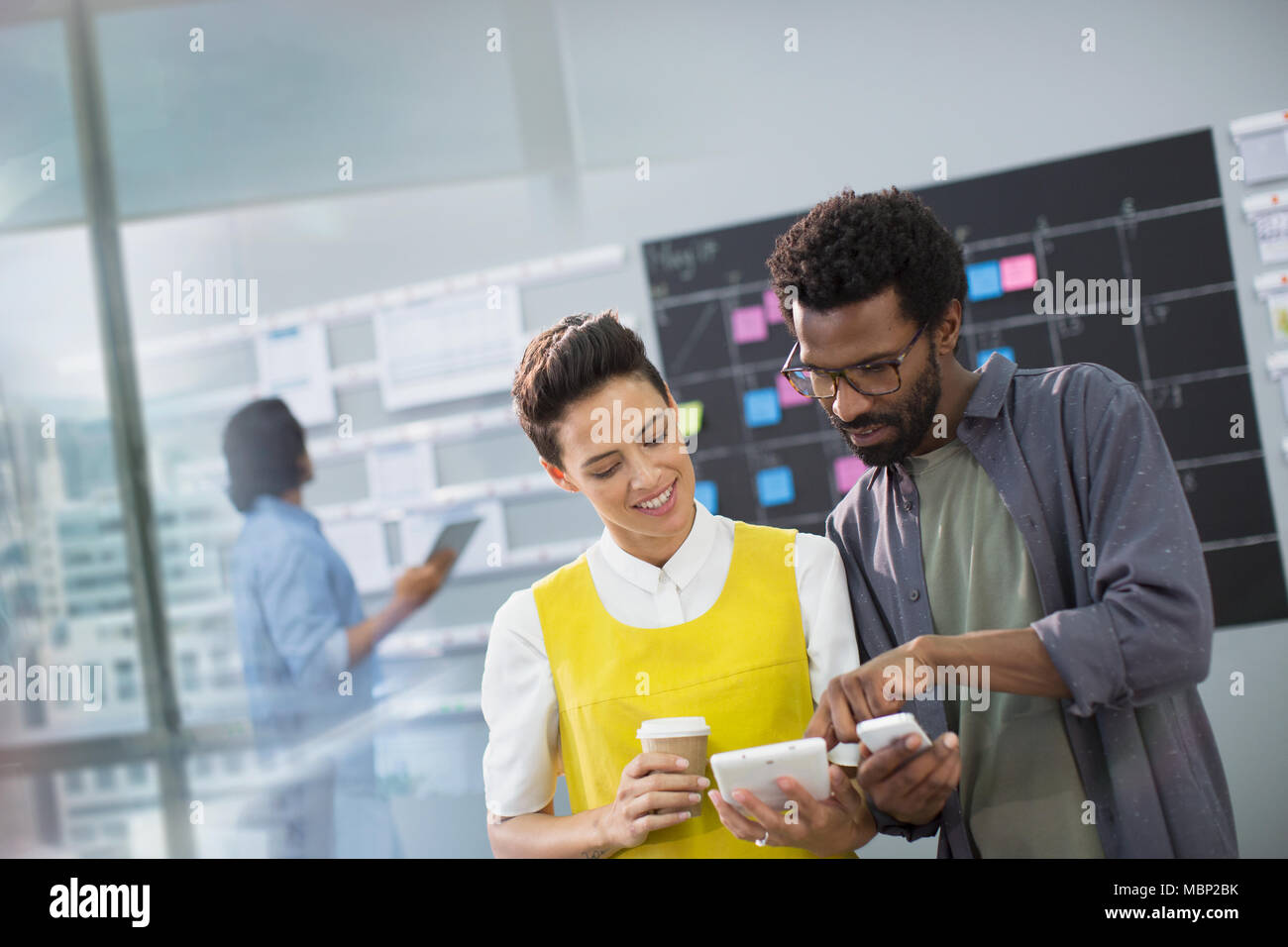 Creative business people using smart phone and digital tablet in office Stock Photo
