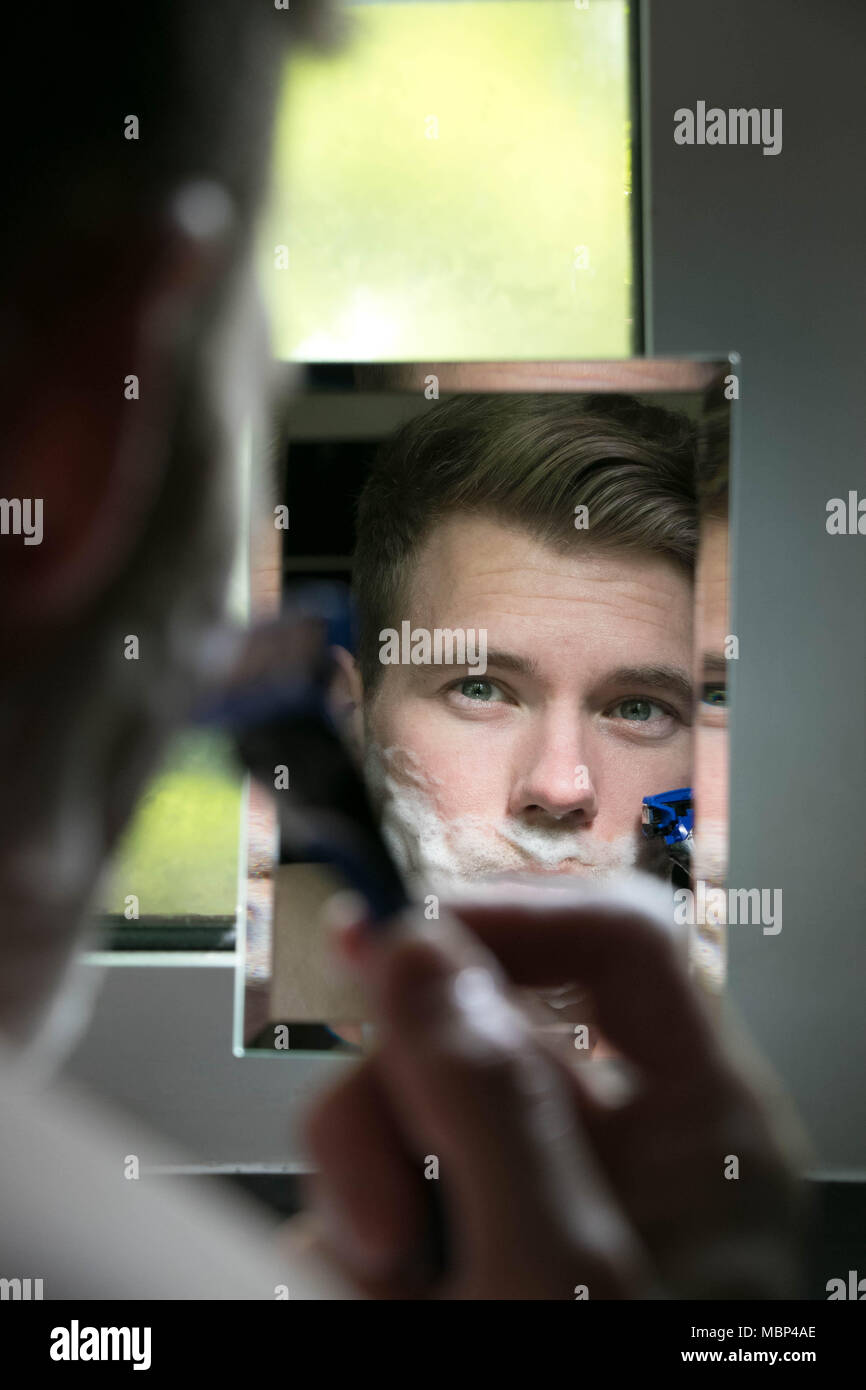 Reflection of handsome man with green eyes shaving with blue razor in small mirror - Stock Image