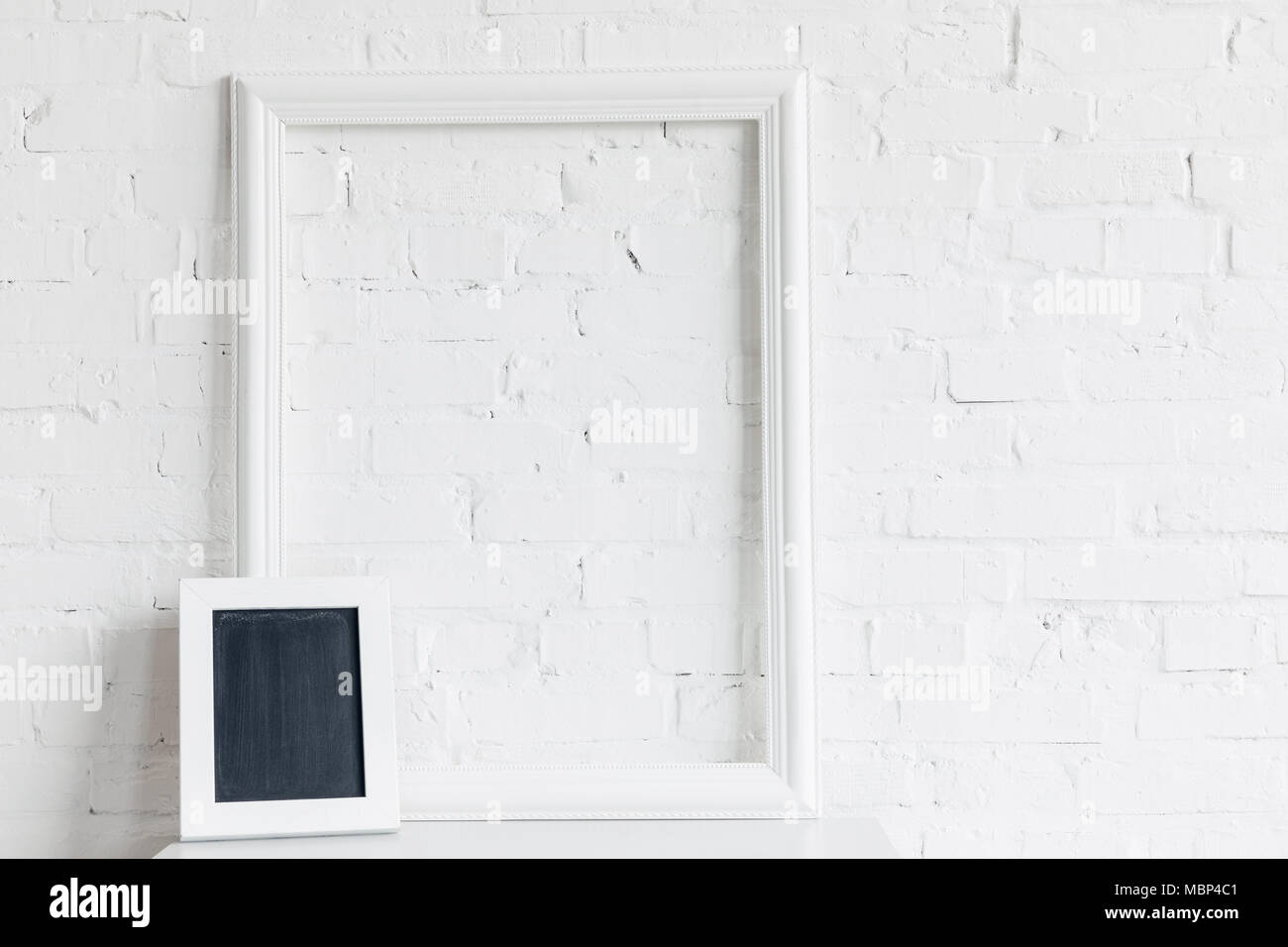 blank frame and small chalkboard in front of white brick wall ...
