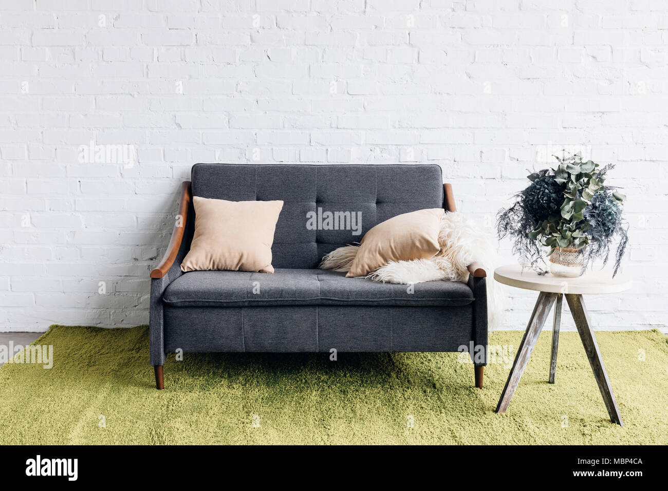 comfy couch in modern living room with white brick wall and flower pot on table, mockup concept - Stock Image