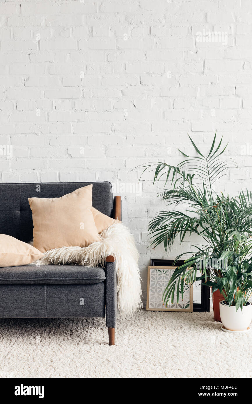 comfy couch with flowerpots in white living room interior with brick wall, mockup concept - Stock Image