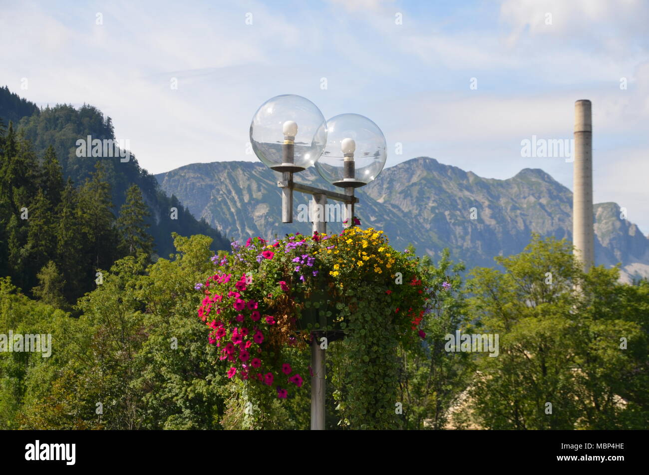view of the lantern on a bridge over the river Lech with flowers and the Alps in the background, Füssen, Bavaria, Germany - Stock Image