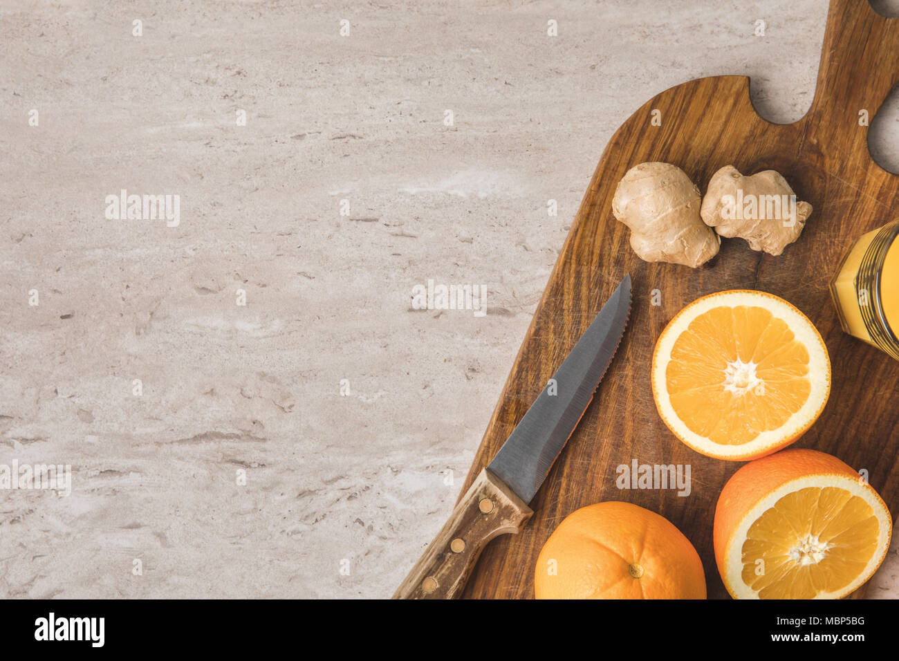 top view of oranges, knife and ginger on marble surface - Stock Image