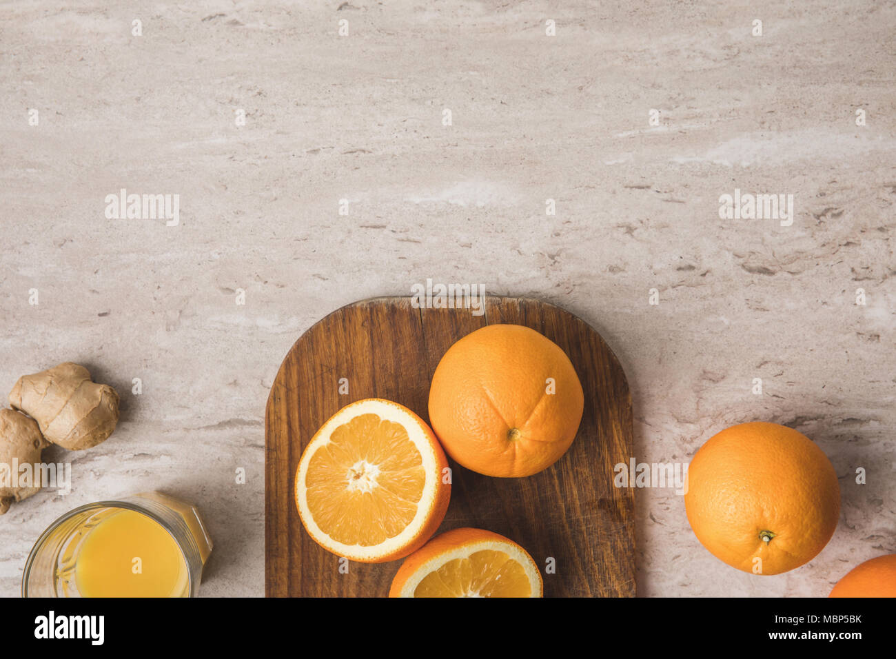 top view of oranges on cutting board on marble tabletop - Stock Image