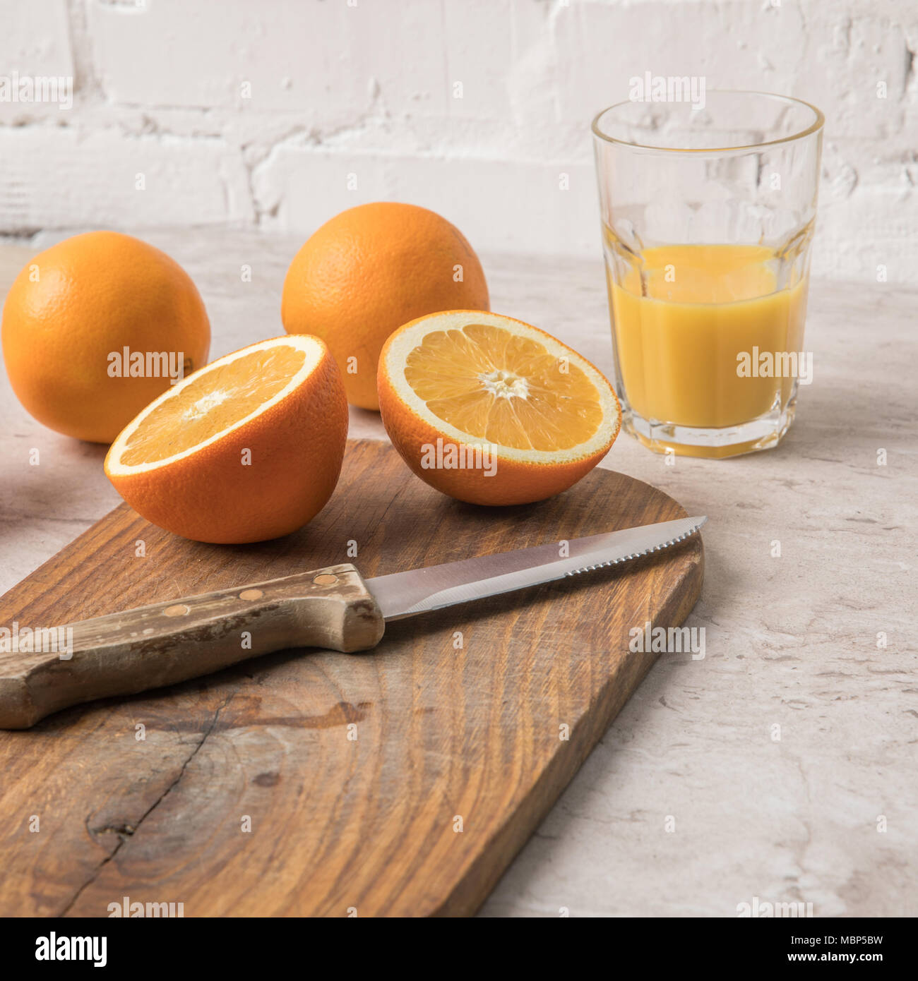 oranges and knife on wooden board on marble table - Stock Image