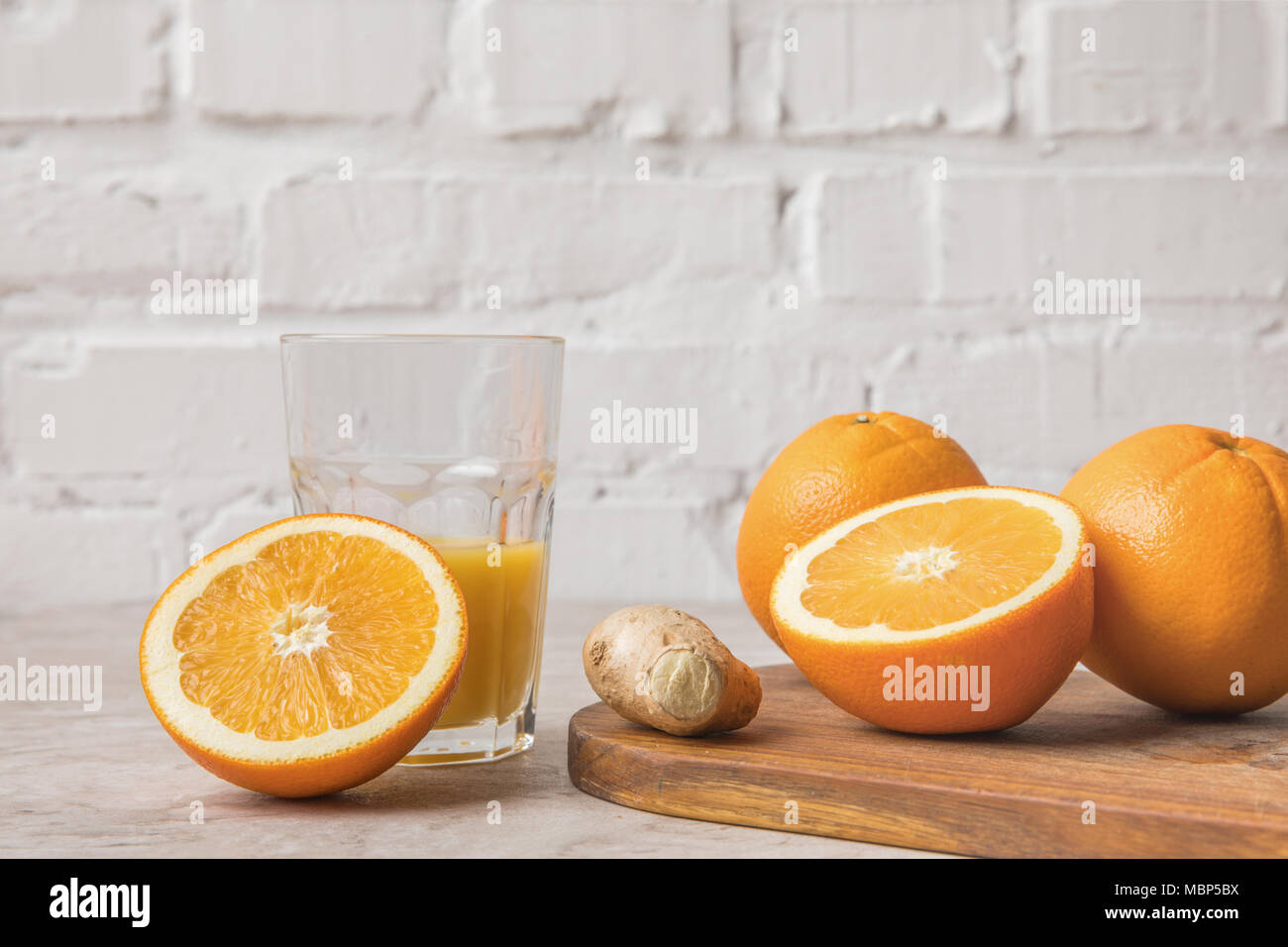 homemade orange juice and oranges with ginger on marble table - Stock Image
