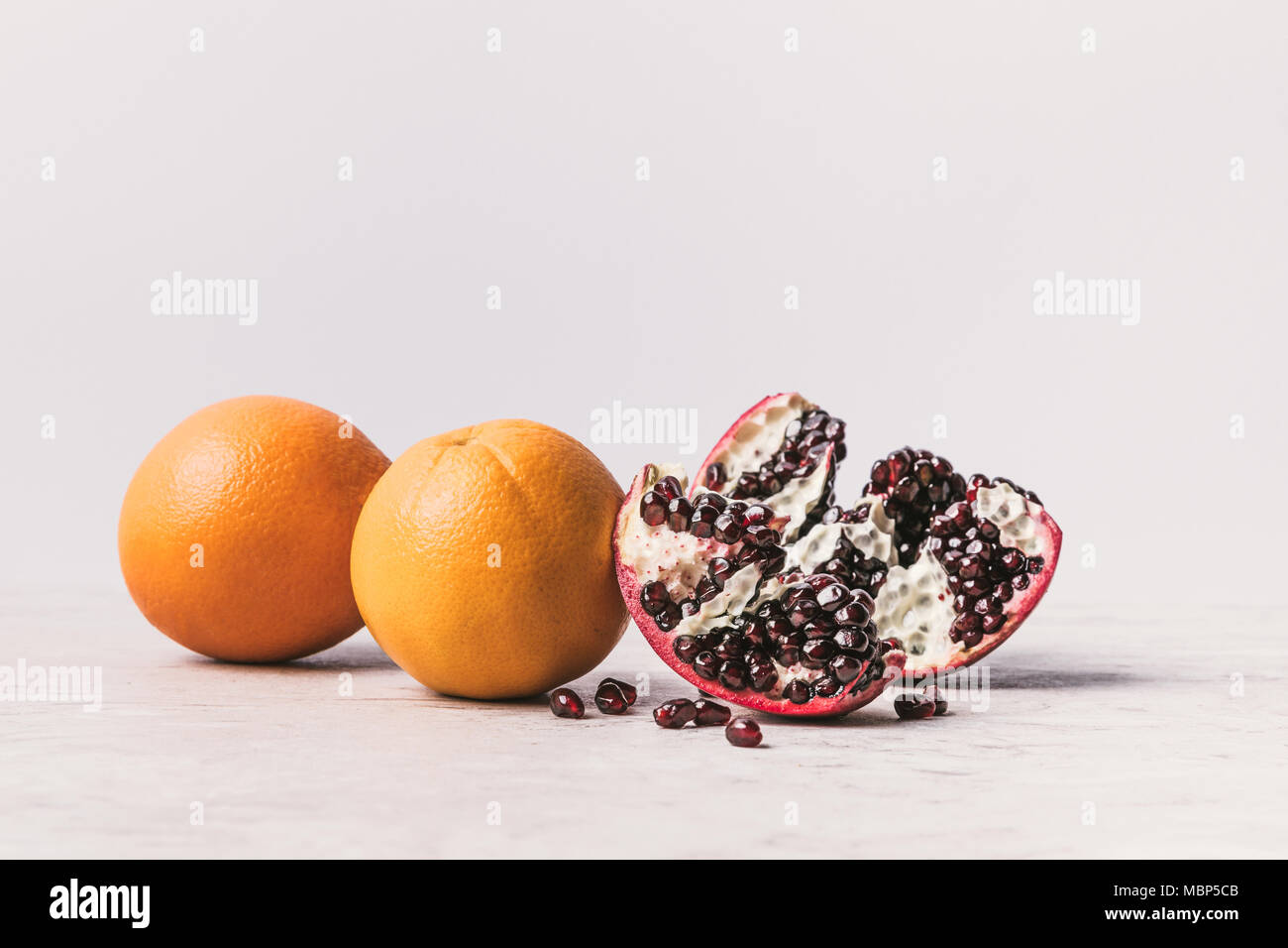 ripe delicious oranges and pomegranate on marble surface - Stock Image