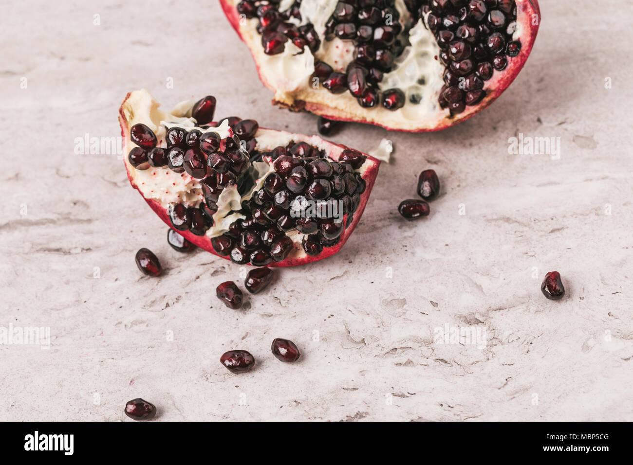 ripe appetizing pomegranate on marble tabletop - Stock Image