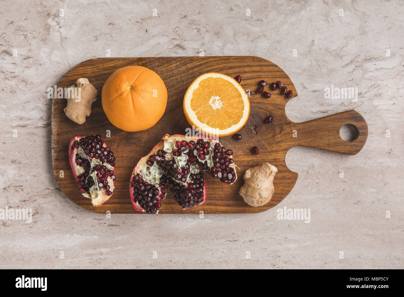 top view of oranges, pomegranate and ginger on cutting board  Stock Photo