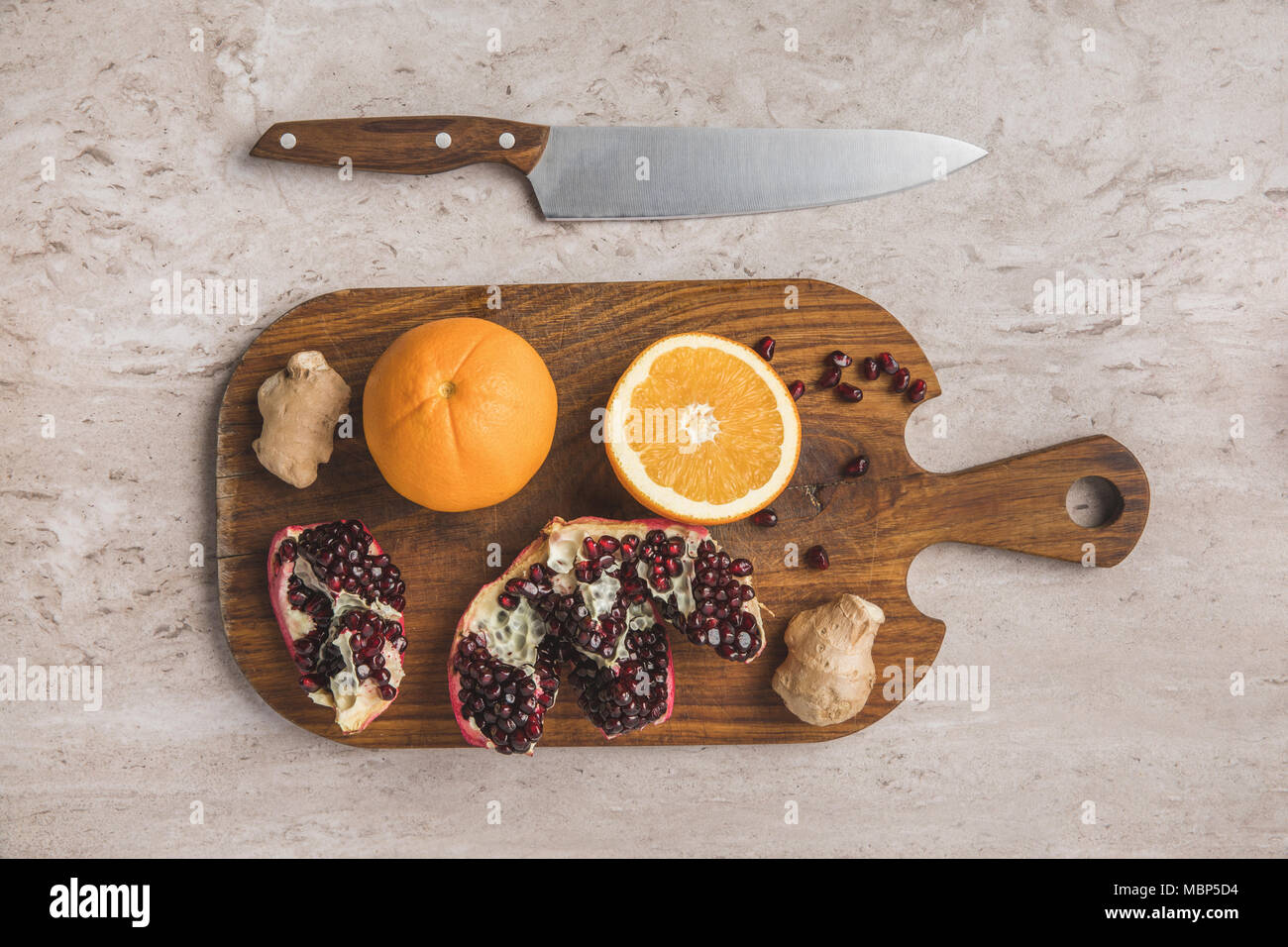 top view of oranges, pomegranate and ginger on cutting board  - Stock Image