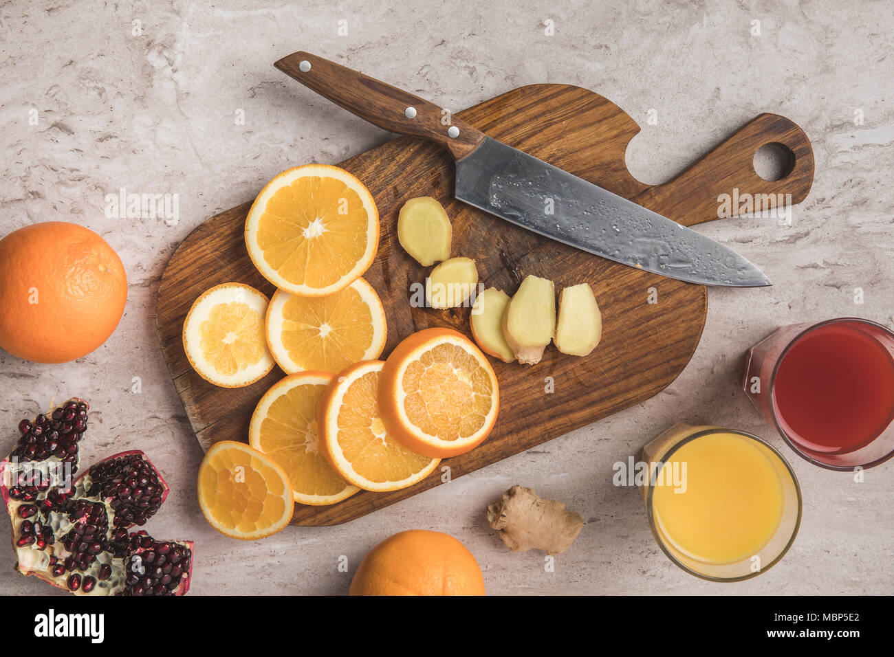 top view of cut oranges, ginger and pomegranate with homemade juices on table - Stock Image