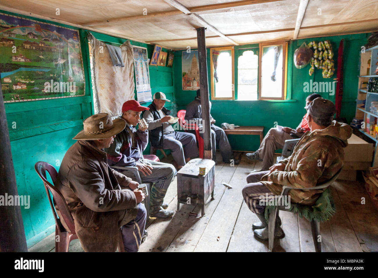 People enjoying tea around Bukhari in small house on the road trip to Bhutan in Himalayas - Stock Image