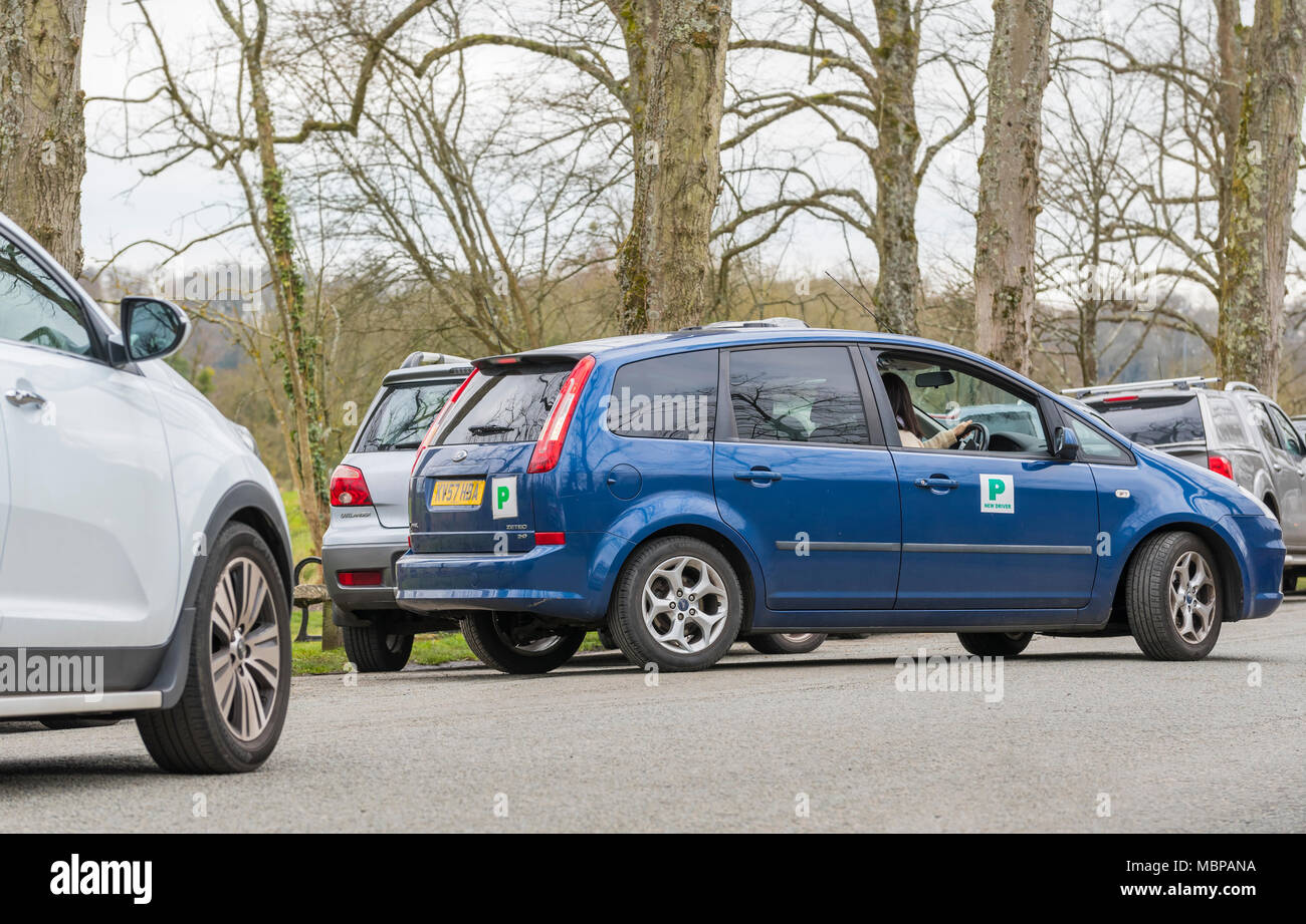 New driver displaying probationary 'P' plates on a car, reverse parking into a tight gap in England, UK. - Stock Image
