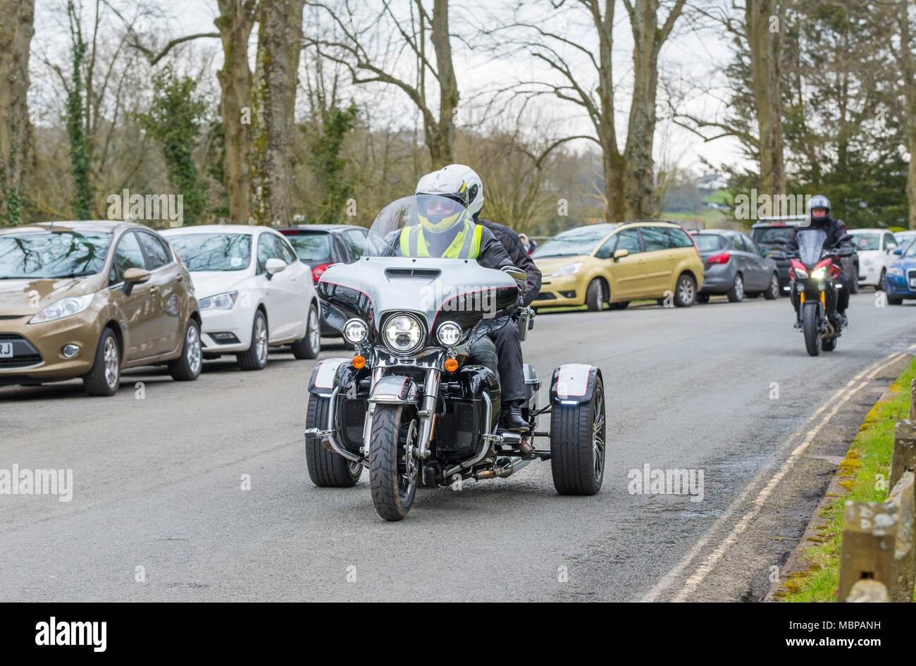 Man riding a Harley Davidson Trike with pillion passenger in the UK. Harley Davidson 3 wheeled motorcycle. Motorbike with 3 wheels. - Stock Image