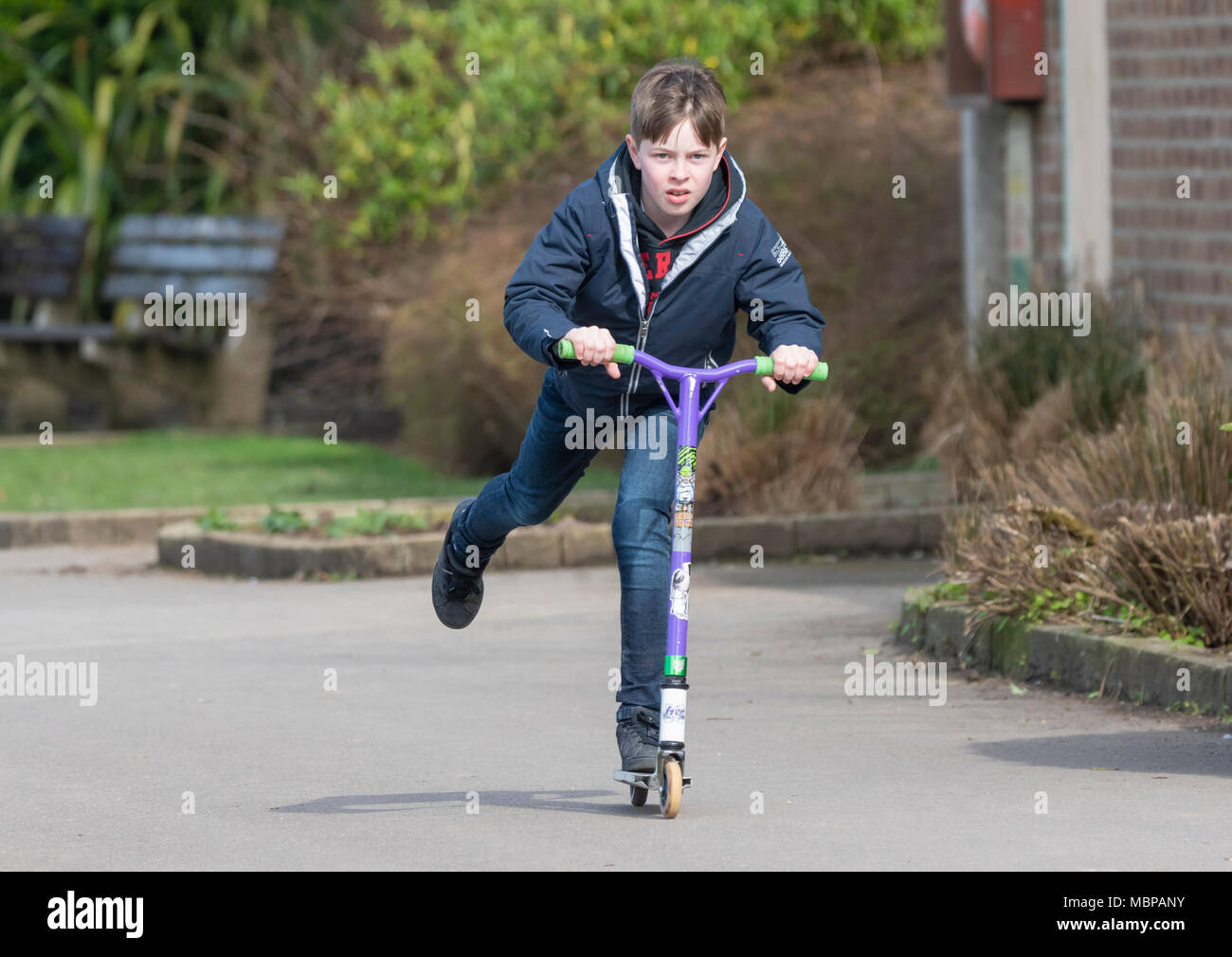 Young boy riding on a scooter around a park in the UK. - Stock Image
