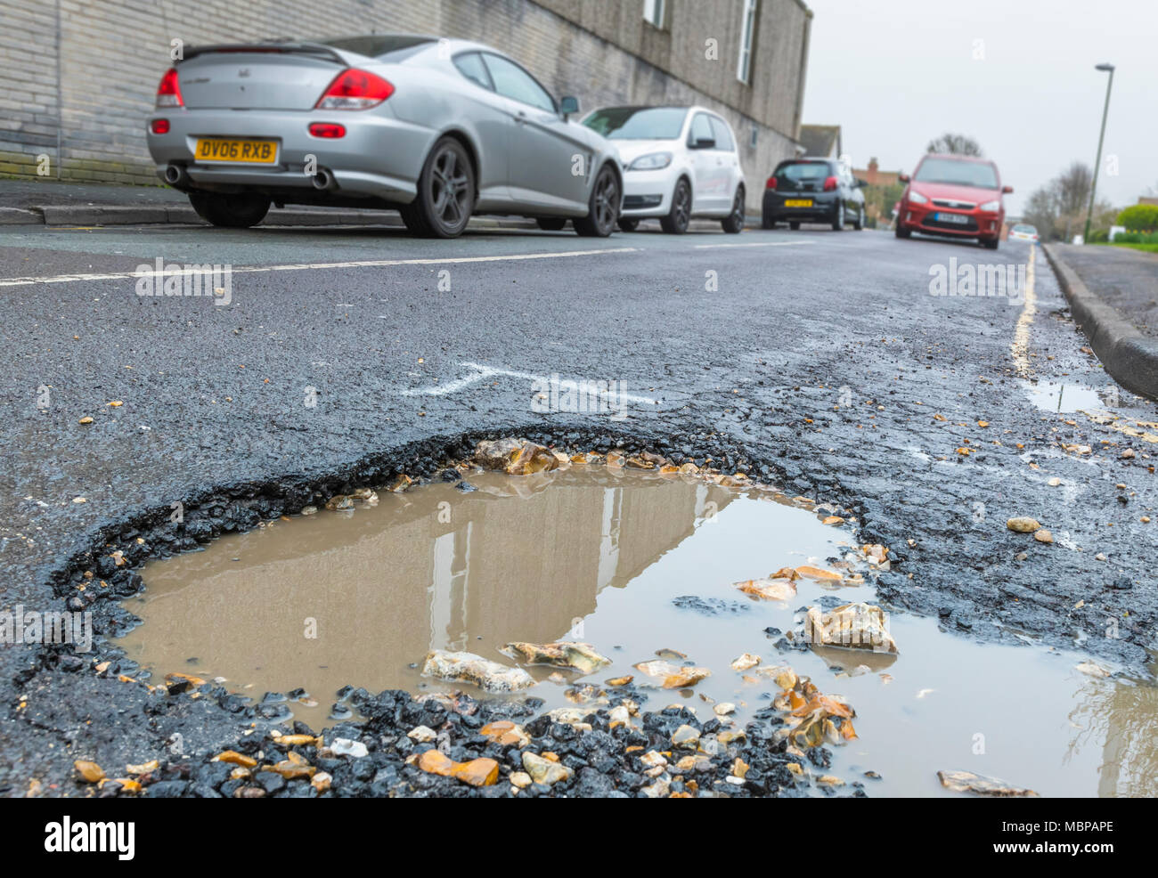 Pothole in an asphalt road filled with rain water in England, UK. Damaged road surface. Road in need or repair. Large potholes. Big pothole. - Stock Image