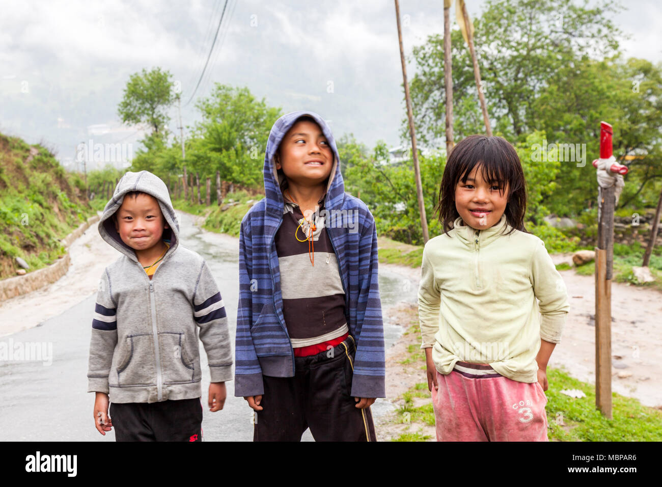 Bhutanese children playing on road seen on the road trip to Bhutan in Himalayas - Stock Image