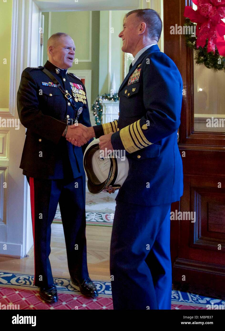 Commandant of the Marine Corps Gen. Robert B. Neller, left, shakes hands with Commandant of the Coast Guard, Adm. Paul F. Zukunft before the 2018 Surprise Serenade at the Home of the Commandants, Washington, D.C., Jan. 1, 2018. The Surprise Serenade is a tradition that dates back to the mid-1800's in which the U.S. Marine Band performs music for the Commandant of the Marine Corps at his home on New Years Day. (U.S. Marine Corps photo by Sgt. Olivia G. Ortiz) Stock Photo