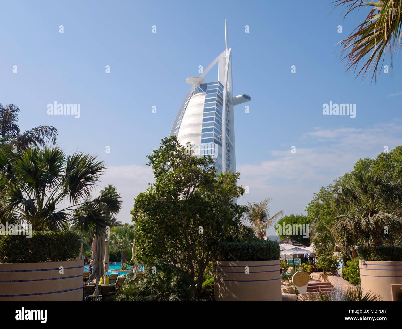 DUBAI,UAE - DECEMBER 18, 2017: The Burj al Arab behind the trees, view from Jumeirah Beach Hotel in Dubai - Stock Image