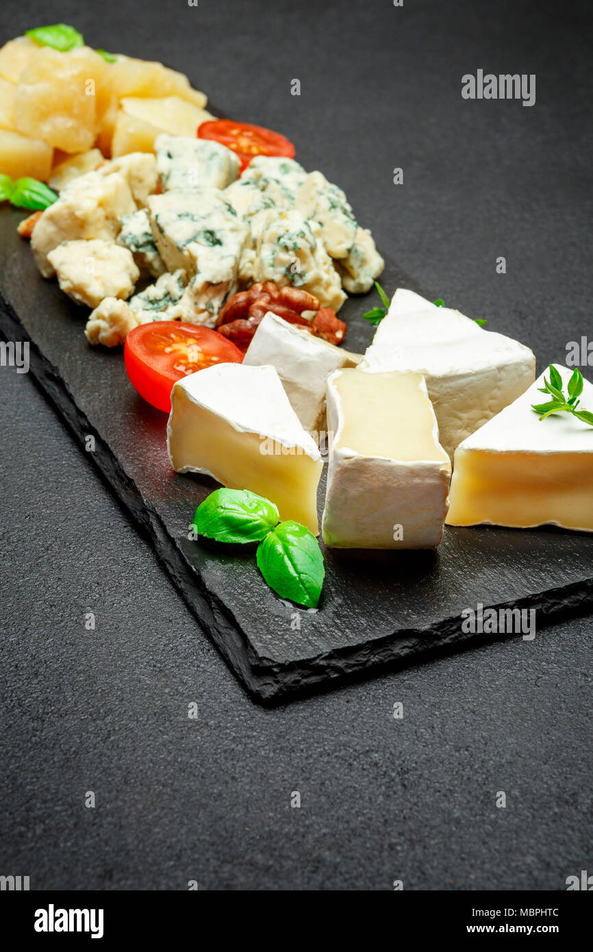Cheese plate with Assorted cheeses Camembert, Brie, Parmesan blue cheese - Stock Image