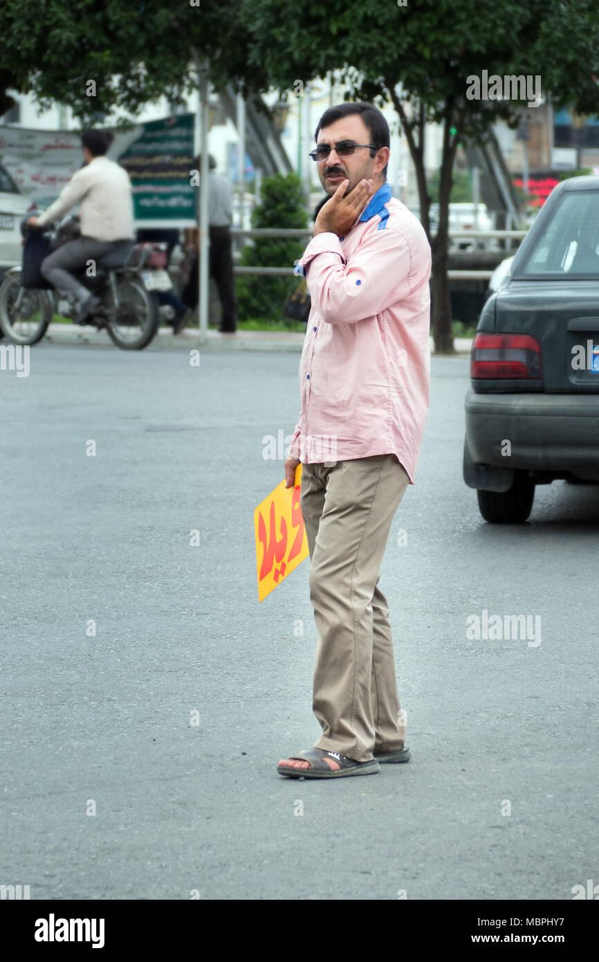 Man holding a sign to advertise house rental along Caspian coast. Babolsar, Iran - Stock Image