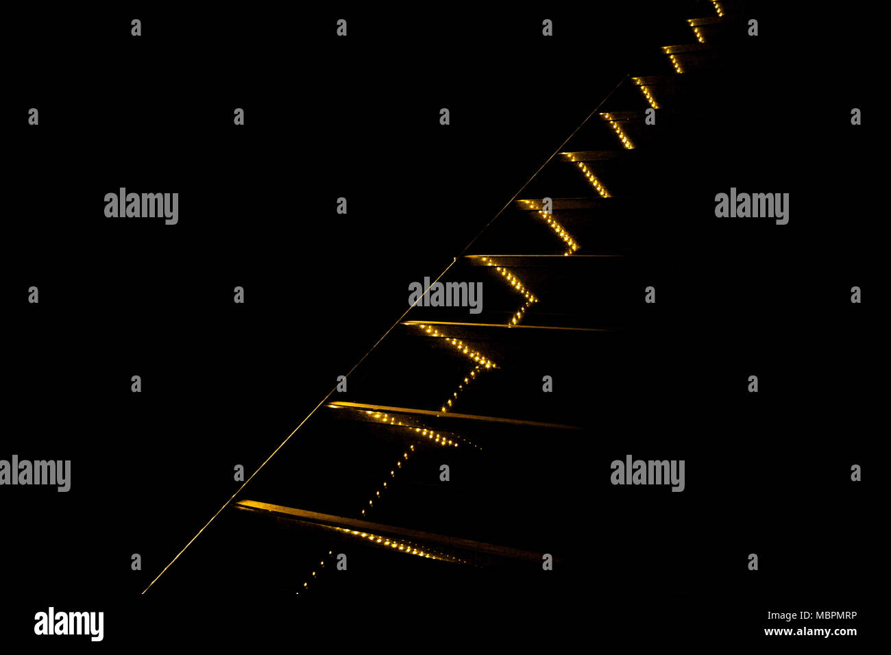 Contrast abstraction. Yellow lights and lines going diagonally upward on black background. - Stock Image