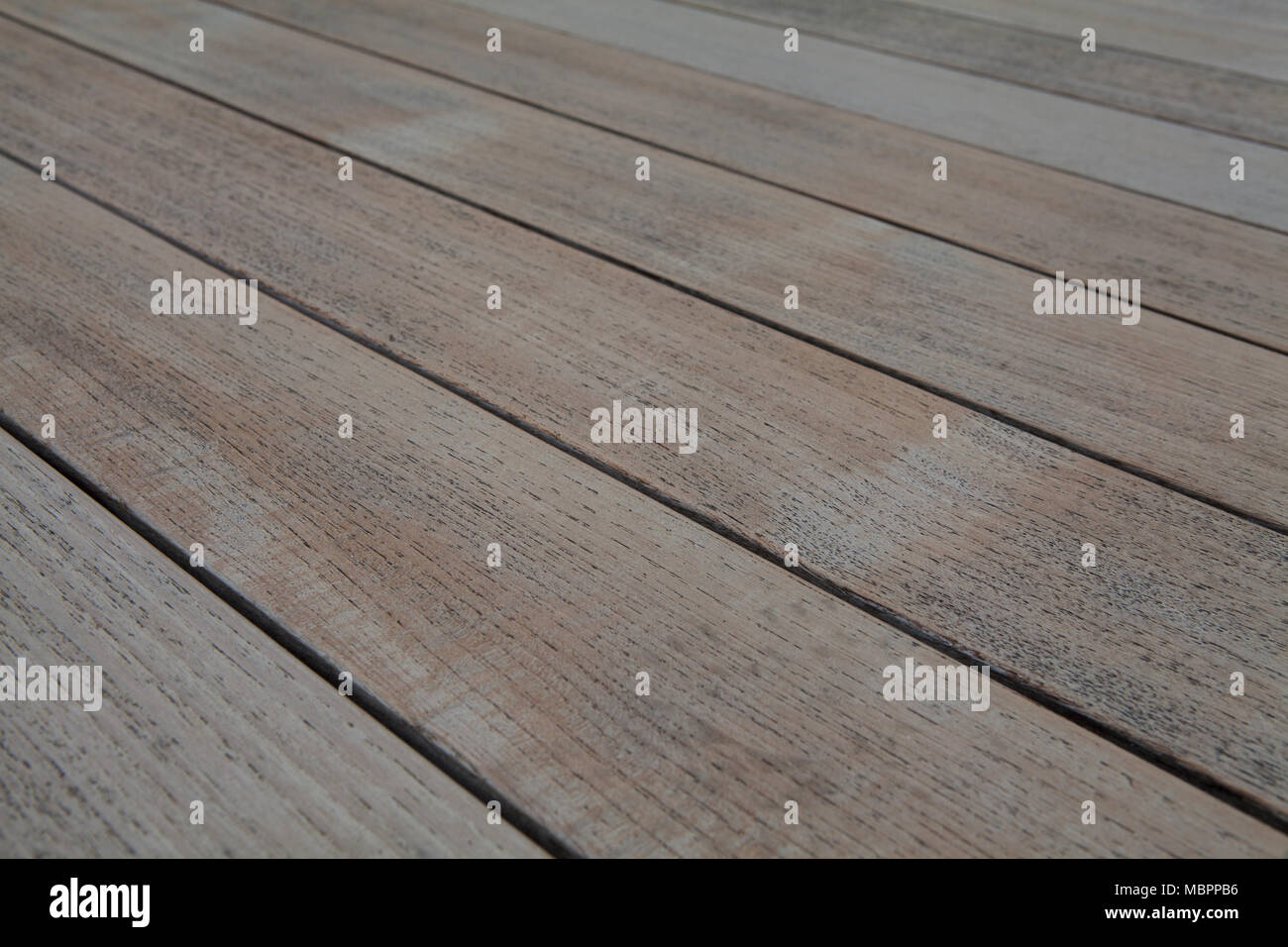 A slightly weathered teak wood garden table, abstract texture, could also be used to illustrate other exterior wooden surfaces including decking - Stock Image