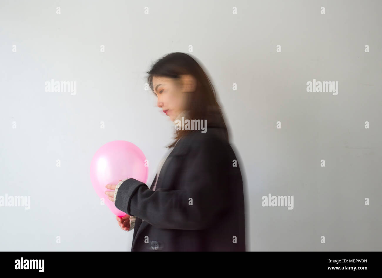 Concept photograph, Young woman blowing a yellow balloon. - Stock Image