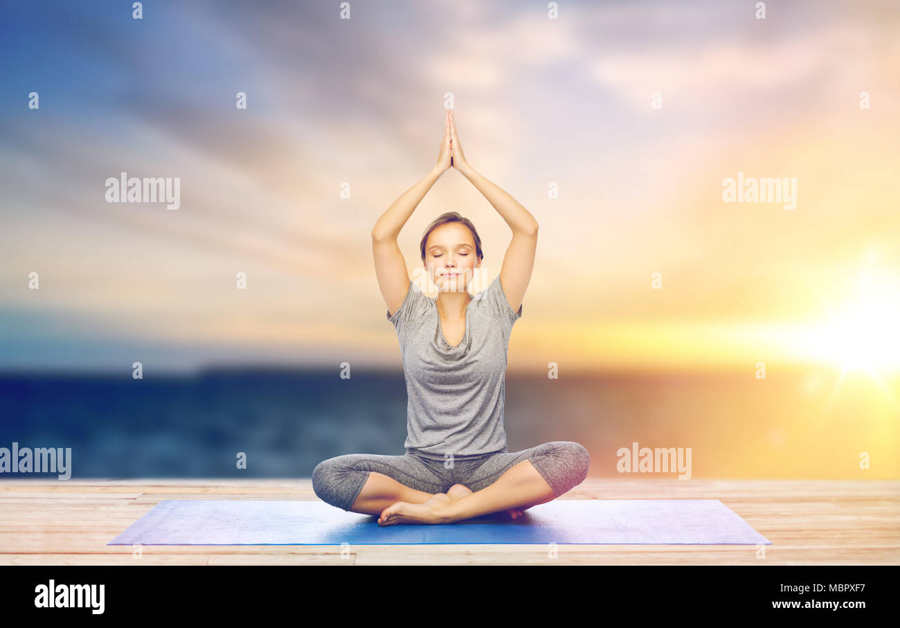 woman meditating in lotus pose on mat outdoors - Stock Image