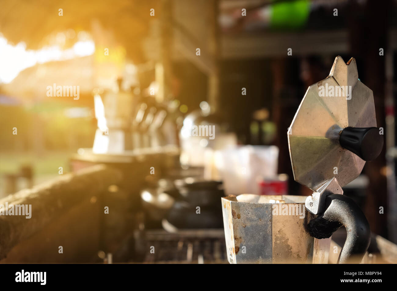 Close up coffee pot old aluminum open breakfast morning market on stove with sunlight - Stock Image